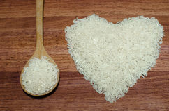 Heart shape of rice on valentine's day, Jasmine rice with wooden spoon. On wooden table (close-up shot), jasmine rice grain, uncooked rice royalty free stock images