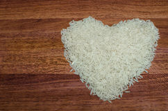 Heart shape of rice on valentine's day, Jasmine rice. Heart shape of rice on valentine's day, Jasmine rice with wooden spoon on wooden table (close-up shot) royalty free stock photos