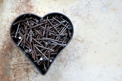 Heart shape with rusted nails. Lots of rusted nails, put together in a heart shape, with spotty background, for Father`s Day, top view Stock Images