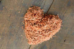 Heart shape of sawdust. On wooden floor Royalty Free Stock Photo