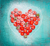 Heart shape sliced Strawberries  on turquoise blue shabby chic wooden background Royalty Free Stock Photos
