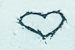 Heart shape on snowy car glass with frash winter snow Royalty Free Stock Image