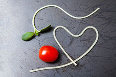 Heart shape of spaghetti and grape tomatoes on Black pan Royalty Free Stock Images