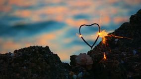 Heart shape sparkler firing in front of movins sea wavws with spot of warm sunset light, love travel concept stock video footage