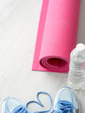 Heart shape Sport shoes, yoga mat, bottle of water on wooden bac. Kground. Sport equipment. Concept healthy life. Selective focus Royalty Free Stock Image