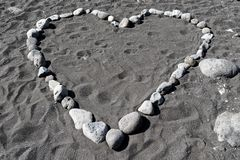 Heart shape from stones in black sand. Praia Formosa beach in Funchal, Portuese island of Madeira royalty free stock photography