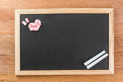 Heart shape from straw on state chalk board. Heart shape made from white pink straw decorate rectangle blank slate chalk board with wooden frame on wooden table stock photos
