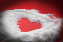 Heart shape in sugar on red Royalty Free Stock Photo