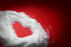 Heart shape in sugar on red Royalty Free Stock Image