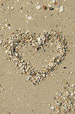 Heart shape symbol made of small sea stones on a beach Royalty Free Stock Photography