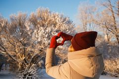 Heart shape symbol of the women mittens in winter frosty day with bushes covered snow on background. Concept of winter. Heart shape symbol of the woman mittens royalty free stock photos