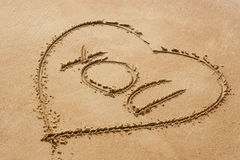 Heart shape symbol with the word you on sandy beac Royalty Free Stock Image