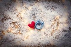 Heart shape toy and Fairy Lights with alarm clock on snow backgr Stock Photos