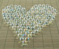 Heart shape of transparent balls. Photo of heart shape made of transparent glass balls over bamboo mat as abstract background Royalty Free Stock Photo