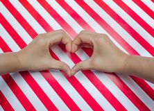 Heart shape of two hand put on striped pattern red & white placemats royalty free stock photo
