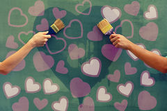 Heart shape on the wall. Young man and woman painting hearts on the concrete wall Royalty Free Stock Images