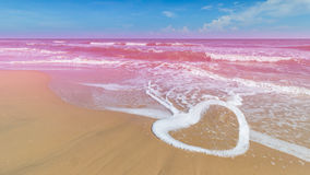 Heart shape of wave with pink sea. Heart shape of wave on the beach with pink sea again blue sky background Royalty Free Stock Image
