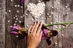 Heart shape of white lilac flowers and hand with ring on wood ta Royalty Free Stock Image