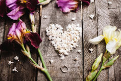 Heart shape of white lilac flowers and ring on wood table Royalty Free Stock Photos