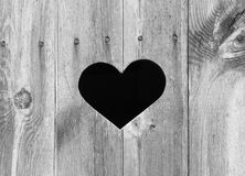 Heart Shape on Wood. Heart shape look out on wooden door to outhouse royalty free stock images
