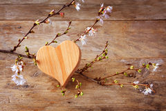 Heart shape of wood with blooming branches on a rustic wooden ba Stock Images