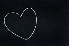 Heart shape written in white chalk. On blackboard stock photography