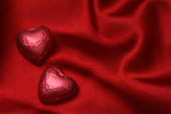 Heart shaped 1. Red heart shaped foiled chocolate on red satin royalty free stock images