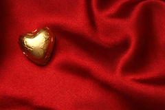 Heart shaped. Foiled chocolate on red satin royalty free stock photo