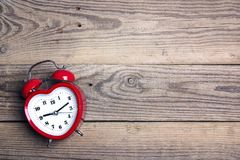 Heart-shaped alarm clock  on old woooden background. Place for t Stock Image