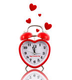 Heart-shaped alarm clock ringing with hearts Royalty Free Stock Photography