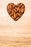Heart shaped almonds on wooden surface background Stock Images