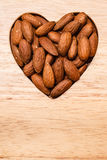Heart shaped almonds on wooden surface background Royalty Free Stock Images