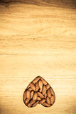 Heart shaped almonds on wooden surface background Royalty Free Stock Photos