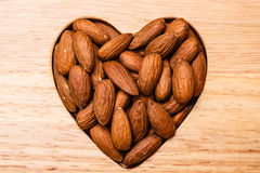 Heart shaped almonds on wooden surface background Royalty Free Stock Photo