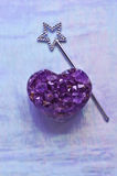 Heart shaped Amethyst with Star Magic Fairy Wand. Amethyst purple gemstone carved into heart shape. Magic silver star wand on pastel textured background of stock images