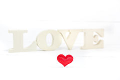 Heart shaped and in the background wooden letters forming word love Royalty Free Stock Image