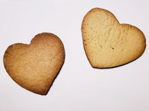 Heart shaped baked biscuits, background and texture. Backdrop for confectionery and cafeteria ads, made from sweet flavored baked pasta, flour based baked food stock photo
