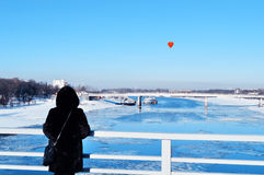 Heart-shaped balloon from the bridge in sunny winter afternoon. Romantic concept. royalty free stock photography