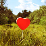 Heart-shaped balloon in a country landscape, with a retro effect Royalty Free Stock Images