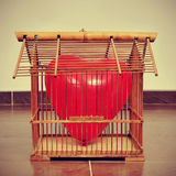 Heart-shaped balloon in an old birdcage, with a retro effect Stock Photos