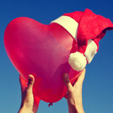 Heart-shaped balloon with a santa hat Royalty Free Stock Photo