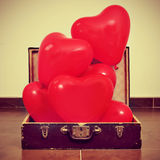 Heart-shaped balloons in an old suitcase Royalty Free Stock Image