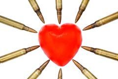 Isolated Heart Attack. A heart shaped bar of soap is surrounded by 5.56 cartridges pointing at it. Fits the concept of 'Heart Attack Royalty Free Stock Photos