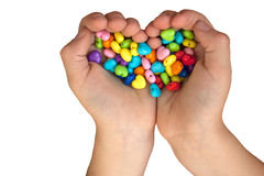 Heart shaped beads in hands  isolated on white. Heart shaped beads in child's hands isolated on white Royalty Free Stock Photos