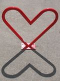 Heart-shaped bike rack and its shadow Royalty Free Stock Photo