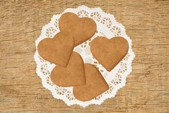 Heart shaped biscuits on lace cloth on wooden table background Royalty Free Stock Photo