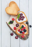 Heart shaped biscuits spread with quark,  cherries and a twig of. Mint presented on a tree disk Stock Photography