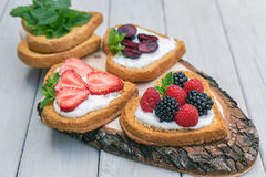 Heart shaped biscuits spread with quark, strawberries, blackberr Stock Images