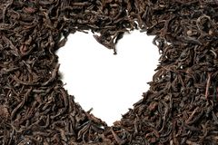 Heart shaped from black leaf tea on white background stock photos