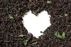Heart shaped from black tea with mint leaves on white background. royalty free stock photos